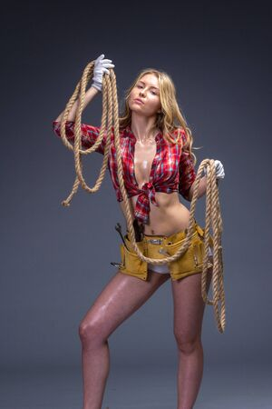 oiled: Pretty woman construction worker with tools belt and rope