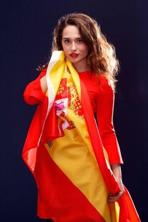 spaniard: Flag of Spain in hands of beautiful woman on blue background. Stock Photo