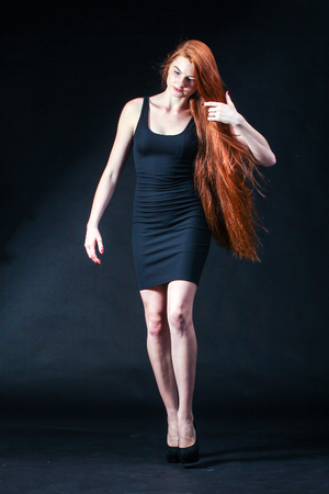 Beauty ginger Girl Portrait. Healthy Long Red Hair. Beautiful Young Woman on black background.