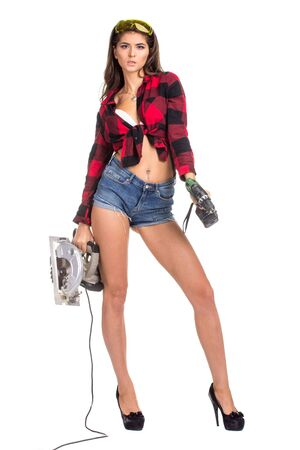 Young sexy brunette woman holding a construction drill and Circular Saw Stock Photo