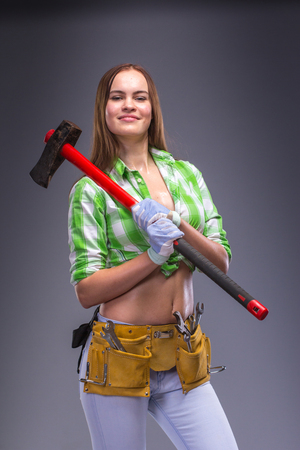 an overalls: Female carpenter worker in overalls holding an axe.