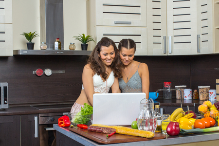 Two attractive twins women looking at laptop, standing in kitchen early morning. Stock Photo
