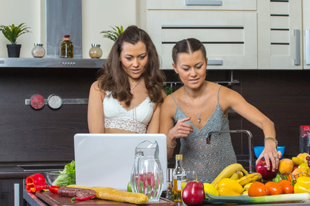 conputer: Two attractive twins women looking at laptop, standing in kitchen early morning. Stock Photo