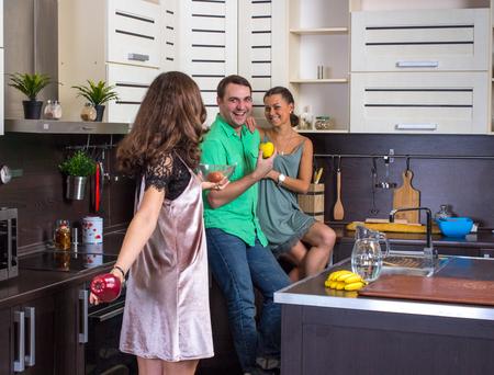 Triángulo amoroso. Mujer que mira a pareja en la cocina.
