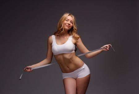 metro de medir: Measuring meter tape in woman hands. Diet and fitness concept healthy lifestyle. Foto de archivo