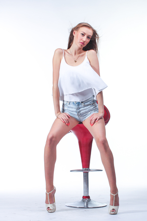 Closeup portrait of young woman in blue short with red bar chair.