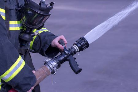 dauntless: Water extingisher in hands, close up view.