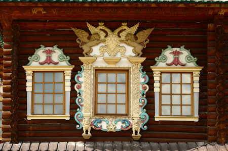 Russian carved wooden frames beautify exterior of timbered house. Stock Photo