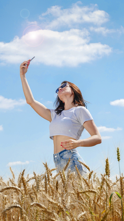 agronomist: Girl in sunglasses doing self photo with her mobile phone on blue sky background.