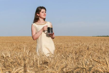 expanse: Young attractive woman in beatiful natural dress walking with with glass of dark beer in the golden wheat field during the sunshine.