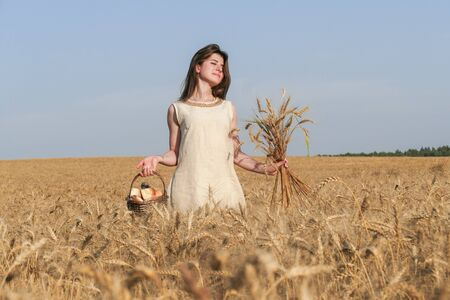 blessedness: Young attractive woman in beatiful natural dress walking with basket with flowers in the golden wheat field during the sunshine.