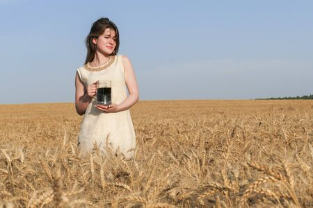 Young attractive woman in beatiful natural dress walking with with glass of dark beer in the golden wheat field during the sunshine.