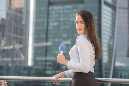 Professional microphone in the hands of an attractive reporter girl working in the background of a business center