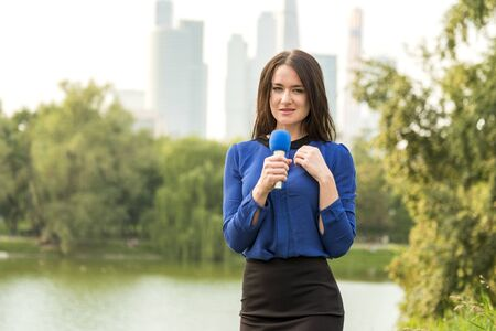 Blue microphone in the hands of a reporter standing in the background of skyscrapers