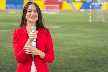 Young attractive journalist is reporting from the stadium online