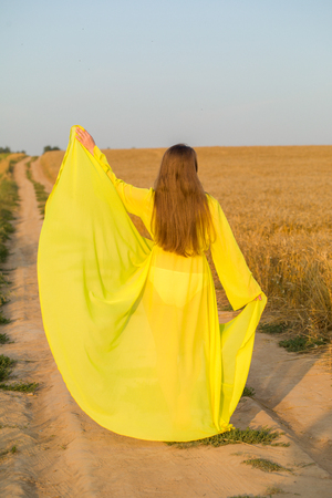 Yellow abaya on pretty woman in golden field. Harvest time. Stock Photo