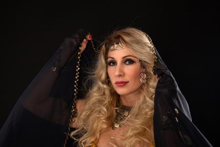 Beautiful blond dancer woman in oriental dress on black background.