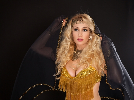 robo: Beautiful blond dancer woman in oriental dress on black background.