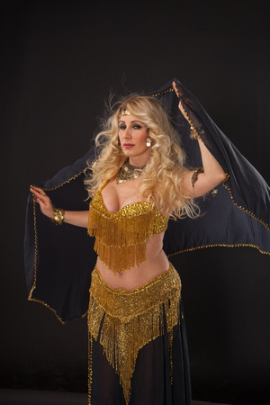 Attractive blond woman in golden dress on black background.