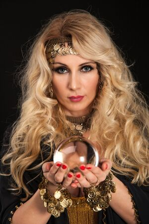 Crystal ball in attractive blond fortune teller hands.