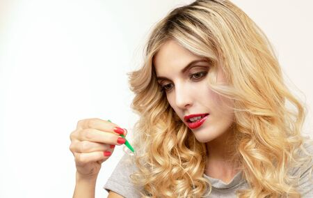 Pretty blonde woman pulls out a tweezers contact lens from the box.