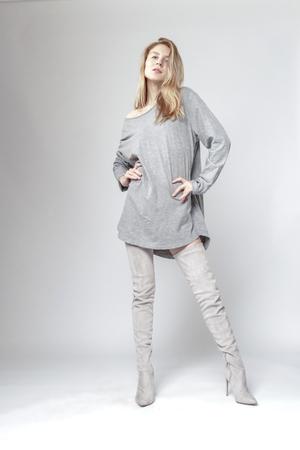 Sehr sexy und stilvolle Frau, die für die Kamera aufwirft. Straßenmode. Sie trägt ein stilvolles graues Hemd und Veloursstiefel.