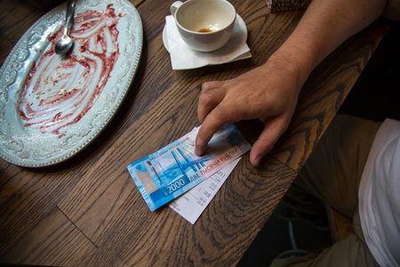 New 2000 rubles banknote in mans hand in cafe. Banco de Imagens