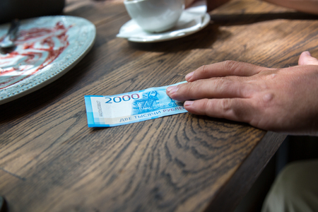 Man holds New 2000 rubles banknote in  hand in cafe.