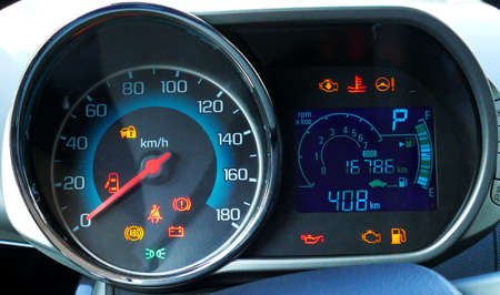 Sustem check on engine start. Speedometer and tachometer with additional instruments on car dashboard.