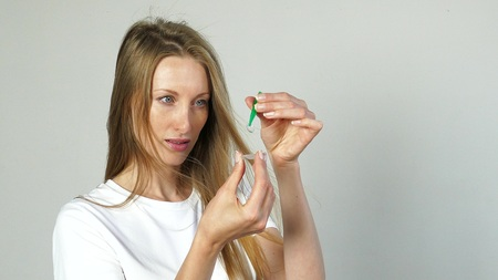 Young woman hold contact lens in her hand, close up portrait. Stock Photo