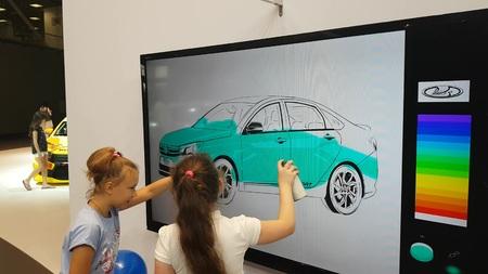 Une fille peint une voiture LADA sur un tableau blanc interactif au salon automobile de Moscou. 03 SEP 2018 MOSCOU, RUSSIE
