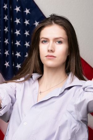 Beautiful caucasian woman with Flag of United States of America on background.