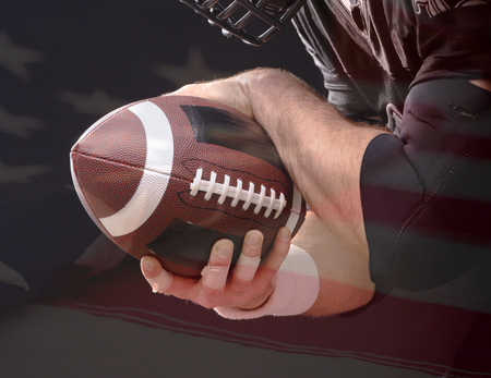 Ball of American Football in footballer hands on US flag background Standard-Bild