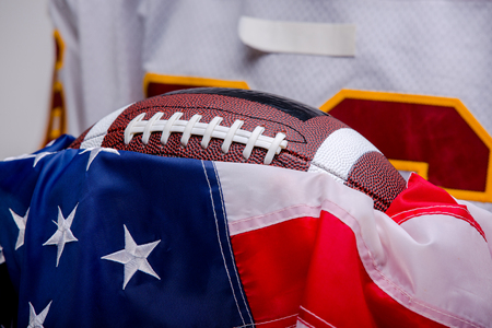 Ball for American football with the national flag in the hands of the player Stock Photo