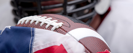 American football ball with the national flag with defocused player on background.