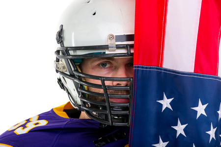 Bearded American football player in blue uniform, under US flag. Close up portrait.