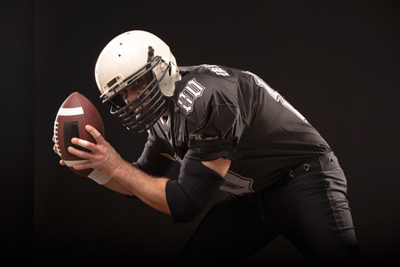 Bearded American football player in black uniform, ready to run close up portrait.