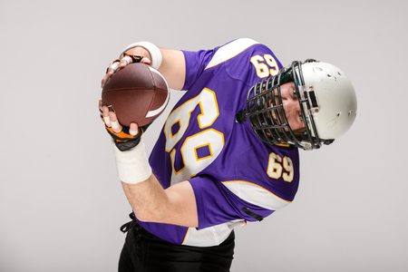 Bearded American football player in black uniform catching the ball, close up portrait. Stock Photo