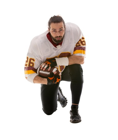Bearded American football player in white uniform sitting on his knee on white bakgroung