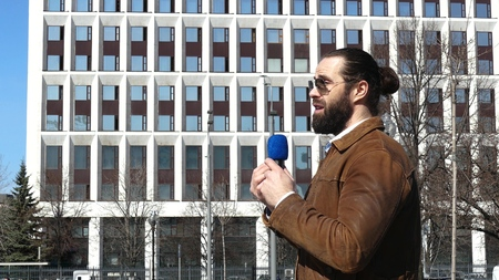A TV journalist is reporting from the city street Stock Photo