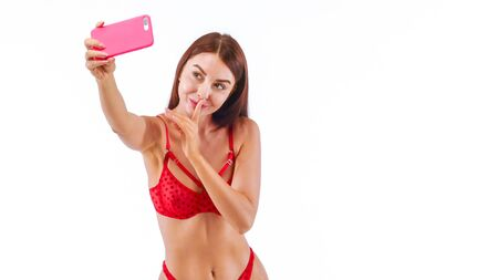 Sexy Woman In red Lingerie Making Selfie Using Smartphone And Smiling. Studio, isolated on white background.