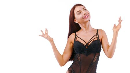 Joyful girl in lacy lingerie looks up waving her arms. Isolated on white.