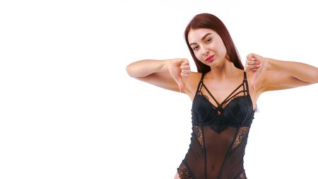 Joyful girl in lacy lingerie shows thumbs down signal to dislike by her fingers. Isolated on white. Stockfoto