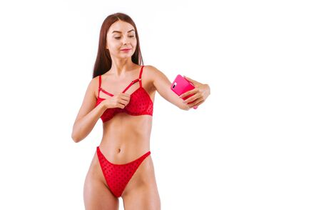 Fitness girl In red Lingerie Making content for her social networks with her body. Studio, isolated image on white background. Stock fotó