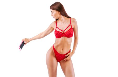 Fitness girl In red Lingerie Making content for her social networks with her body. Studio, isolated image on white background. Stok Fotoğraf