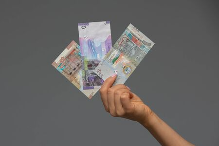 Kuwaiti dinar banknote in hand of young woman. Kuwaiti dinar is the national currency of Kuwait