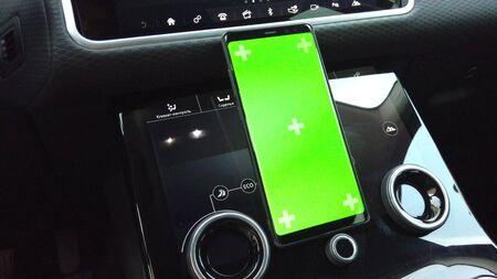 Modern green screen smartphone in car on dashboard background