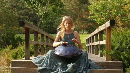 Woman Is Playing On The Steel hanf Drum. Close-Up. Tank Drum 版權商用圖片