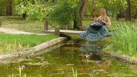 Woman Drummer Playing Music Instrument Hang in park 版權商用圖片