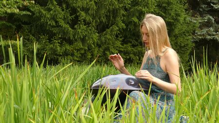 Girl plays in the green field on a hangpan 版權商用圖片